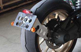 ドリルド加工が施されたシンプルで小振りなナンバープレートホルダーはキャッツアイテールとウインカーをセット。
